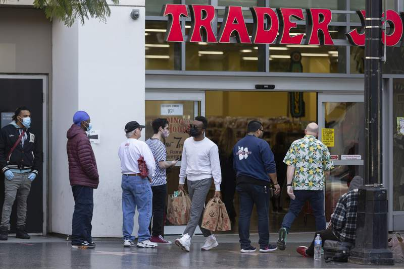 People stand in line, but leaving space to the neighboring person, while waiting to enter a Trader Joe's grocery store in the Hollywood section of Los Angeles on Tuesday, March 24, 2020. (AP Photo/Damian Dovarganes)