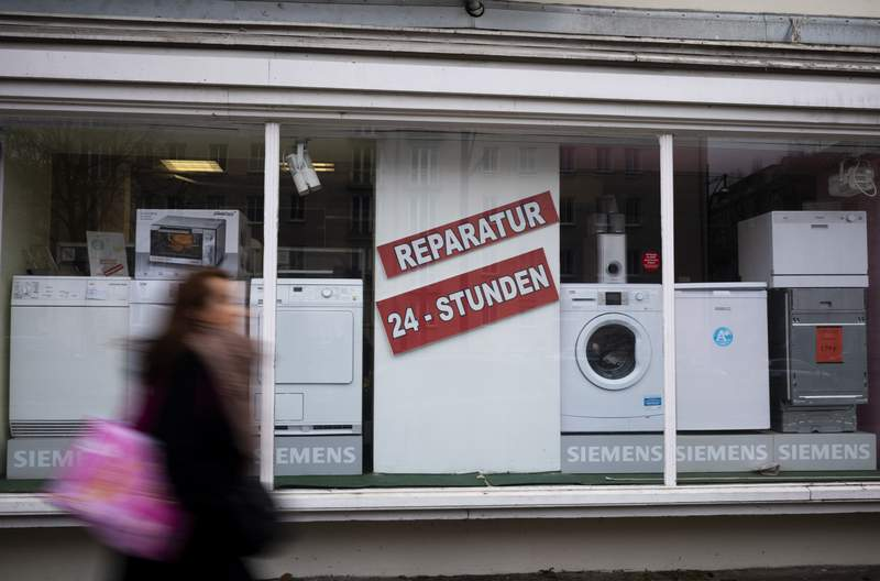 A person walks past a shop offering the repair of electronic equipment and domestic appliances in Berlin, Germany, Friday, Feb. 26, 2021. Companies that sell refrigerators, washers, hairdryers or TVs in the European Union will need to ensure those appliances can be repaired for up to 10 years. The new 'right to repair' comes into force across the 27-nation bloc Monday, March 1, 2021. The posters read: ' Repair - 24 hours'. (AP Photo/Markus Schreiber)