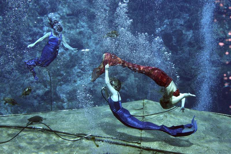 FILE - In this Aug. 16, 2007 file photo, performers with the Weeki Wachee mermaid attraction practice in Weeki Wachee, Fla. Florida Gov. Ron DeSantis has signed legislation dissolving the city of Weeki Wachee, known for its mermaid shows. The mermaids at Weeki Wachee State Park have been a staple of Florida tourism since 1947.   (George Skene/Orlando Sentinel via AP, File)