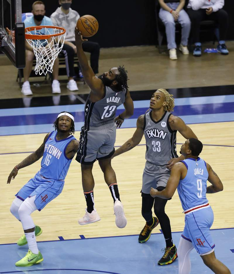 Brooklyn Nets' James Harden drives to basket for a layup past Houston Rockets' Ben McLemore, left, during the second quarter of an NBA basketball game Wednesday, March 3, 2021, in Houston. (Bob Levey/Pool Photo via AP)