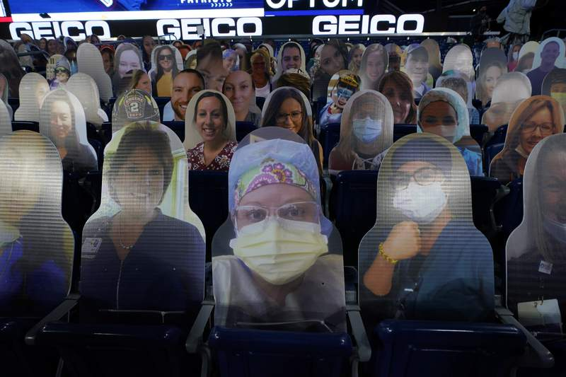 FILE - Cutout photos of people, including first responders and healthcare workers, sit in seats in Gillette Stadium before an NFL football game between the New England Patriots and the Buffalo Bills in Foxborough, Mass., in this Monday, Dec. 28, 2020, file photo. The NFL says 7,500 health care workers vaccinated for the coronavirus will be given free tickets to next months Super Bowl to be played in Tampa, Florida. NFL Commissioner Roger Goodell also said in a news release Friday that attendance at the Feb. 7 game would be limited to those workers and about 14,500 other fans.(AP Photo/Charles Krupa, File)