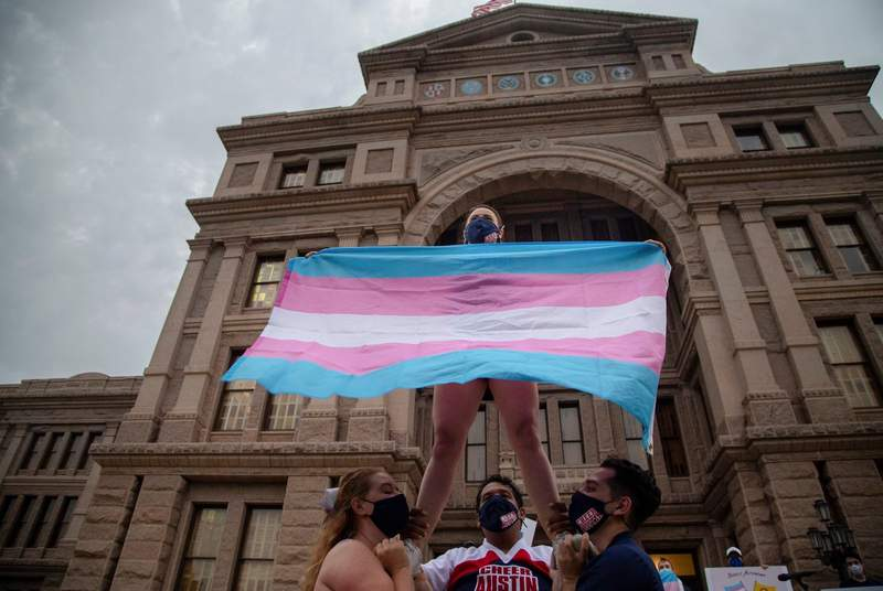 Ali Cross of the Austin Cheer squad waves a trans flag while her squad mates hold her up on the steps of the state Capitol at a rally against anti-trans legislation on April 28, 2021.