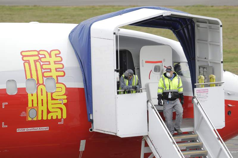 FILE - In this April 21, 2020, file photo, Boeing Co. workers wearing masks stand near an entry door to a 737 Max airplane owned by China-based Lucky Air, in Renton, Wash. China isnt ready to join the United States in approving Boeings 737 Max to return to flying following a two-year grounding prompted by a pair of fatal crashes, a regulator said Monday, March 1, 2021.  (AP Photo/Ted S. Warren, File)