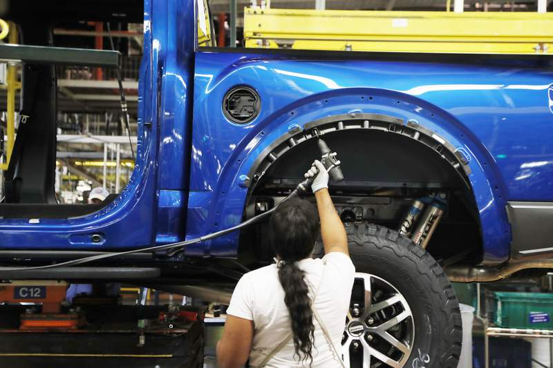 FILE- In this Sept. 27, 2018, file photo a United Auto Workers assemblyman works on a 2018 Ford F-150 truck being assembled at the Ford Rouge assembly plant in Dearborn, Mich. Ford Motor Co. said Thursday, Feb. 4, 2021, that it will cut shifts at two of its U.S. manufacturing plants next week, due to the worldwide chip shortage that has also impacted other automakers. Ford will cut shifts at its Dearborn, Mich., facility and  Kansas City, Mo., plant; both produce the F-150 pickup truck, Ford's most popular model and part of the F-Series, the top-selling vehicle in the U.S. (AP Photo/Carlos Osorio, File)