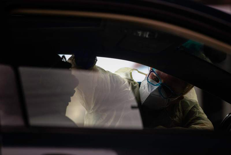A nurse conducts a swab test for COVID-19 on a patient in a drive-thru station at the Austin Emergency Center at Mueller on Jan. 25, 2021. Since the fall, the CDC says there have been several new variants identified worldwide: A UK variant (B.1.1.7), a South African variant (B1.351) and a Brazilian variant (P.1).                    Credit: Evan L'Roy/The Texas Tribune