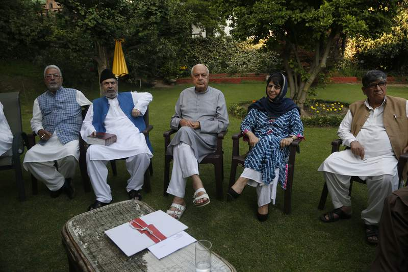 FILE - In this Sunday, Aug. 4, 2019, file photo, National Conference (NC) President Farooq Abdullah, center, Peoples Democratic Party (PDP) leader Mehbooba Mufti, second right, and other leaders sit during an all parties meeting in Srinagar, India. Half a dozen political parties, including NC and PDP, vowed Saturday, Aug. 22, 2020, to fight for restoration of the special status that was stripped last year from Indian-administered Kashmir, setting off widespread anger and economic ruin amid a harsh security clampdown. Four pro-India Kashmiri political parties and two Indian political parties, including the main opposition Congress Party, said in a joint statement that Indias move unrecognizably changed the relationship between the region and New Delhi. (AP Photo/Mukhtar Khan)