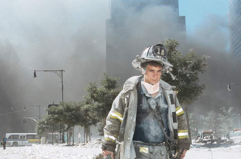 An unidentified New York City firefighter walks away from Ground Zero after the collapse of the Twin Towers.