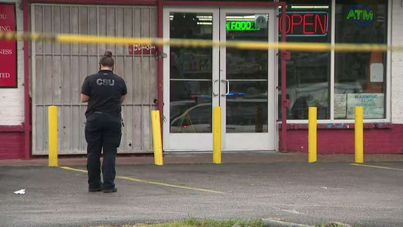 A crime scene investigator photographs a homicide scene outside a convenience store in the 2700 block of Alabama Street in Houston on Nov. 9, 2020.