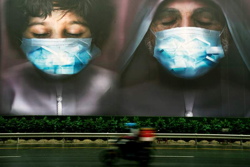 FILE - In this April 15, 2020 file photo, a billboard urges people to stay home during the coronavirus pandemic in Dubai, United Arab Emirates. Middle East economies are recovering from the coronavirus pandemic faster than anticipated, largely due to the acceleration of mass inoculation campaigns and an increase in oil prices. But the International Monetary Fund warned Sunday, April 11, 2021, that an uneven vaccine distribution would derail the region's rebound, as the prospects of rich and poor countries diverge. (AP Photo/Jon Gambrell, File)