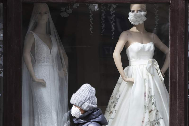 A woman wearing face mask to protect against coronavirus walks past the closed bridal shop with a mannequin decorated with face masks, in Moscow, Russia, Monday, April 6, 2020.  The new coronavirus causes mild or moderate symptoms for most people, but for some, especially older adults and people with existing health problems, it can cause more severe illness or death. (AP Photo/Pavel Golovkin)