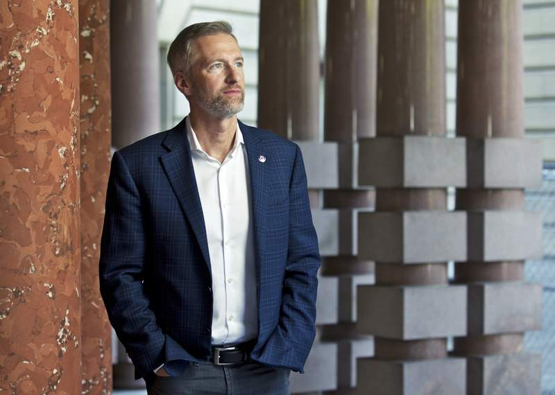 FILE - In this Aug. 5, 2019, file photo, Portland Mayor Ted Wheeler poses for a photo in Portland, Ore. As the city has been wracked by violent protests for weeks, Wheeler has faced criticism from all sides. (AP Photo/Craig Mitchelldyer, File)