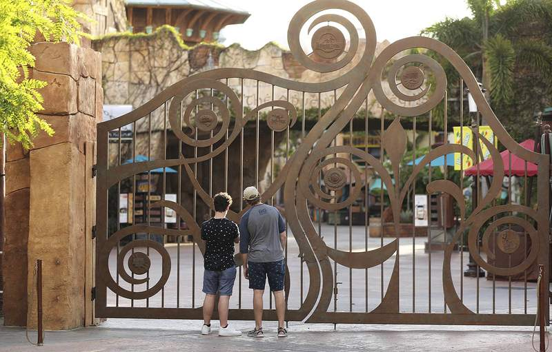 FILE - In this Thursday, May 14, 2020, file photo, guests peer through the closed gate to Universal's Islands of Adventure beside Universal CityWalk, in Orlando, Fla. Universal Orlando is aiming to reopen its theme parks in early June, a resort official said Thursday, May 20, more than two months after the company joined crosstown rival Disney World in closing the gates to stop the spread of the new coronavirus. (Stephen M. Dowell/Orlando Sentinel via AP, File)