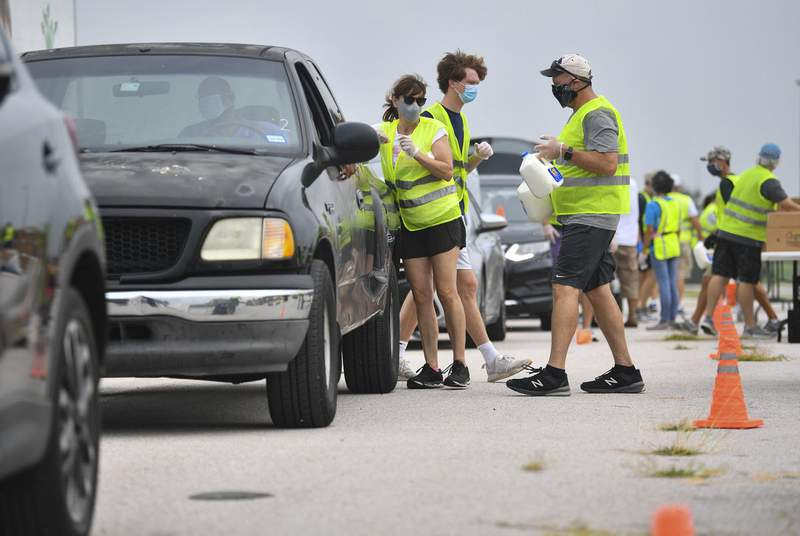 Volunteers load boxes of food into a car during a drive-thru food distribution hosted by the Central Texas Food Bank in Austin in June. As Congress debates a new coronavirus relief package, out-of-work Texans are struggling to make ends meet.                    Credit: Allie Goulding/The Texas Tribune