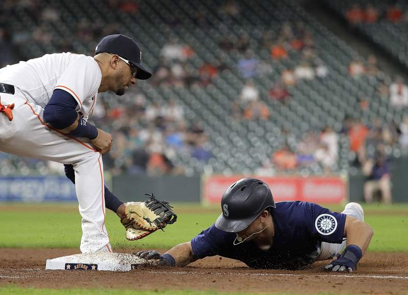 HOUSTON, TEXAS - APRIL 28: Sam Haggerty #0 of the Seattle Mariners dives back into first base as Yuli Gurriel #10 of the Houston Astros applies the tag in the seventh inning at Minute Maid Park on April 28, 2021 in Houston, Texas. (Photo by Bob Levey/Getty Images)