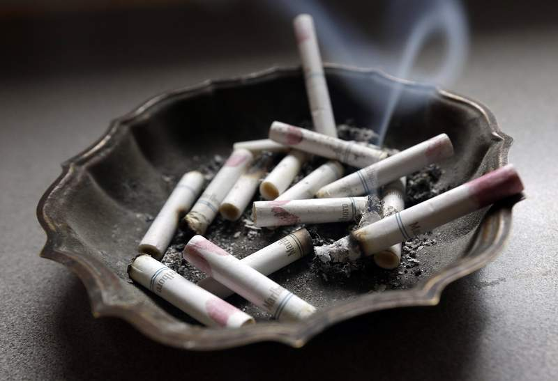 FILE - In this Saturday, March 2, 2013 file photo, a cigarette burns in an ashtray in Hayneville, Ala. Anti-smoking advocates are warning that the stress and disruptions of the COVID-19 pandemic may have slowed efforts to get more Americans to quit in 2020. (AP Photo/Dave Martin)
