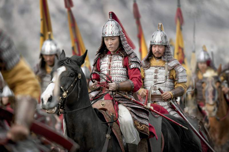 """This image released by Disney shows Yifei Liu, center, in the title role of """"Mulan.""""  (Jasin Boland/Disney via AP)"""