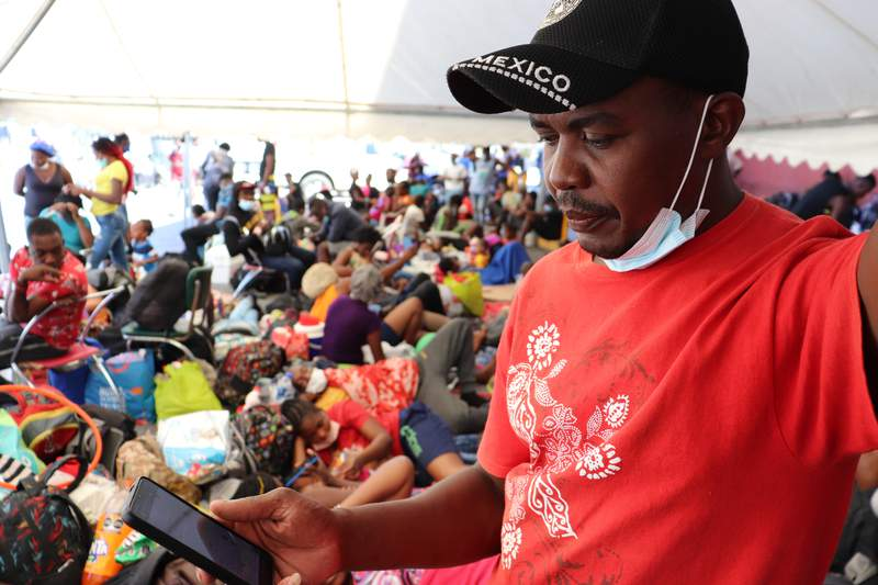 Selomourd Menrrivil, from Cap-Haitien, Haiti, looks at his cell phone as he gathers with other migrants in Monterrey, Mexico, Thursday, Sept. 23, 2021. Menrrivil, 43, continued receiving daily updates all week from other Haitians in Del Rio and Ciudad Acua, after arriving with his wife and two teen daughters, and has decided to legalize his status in Mexico. (AP Photo/Marcos Martinez Chacon)