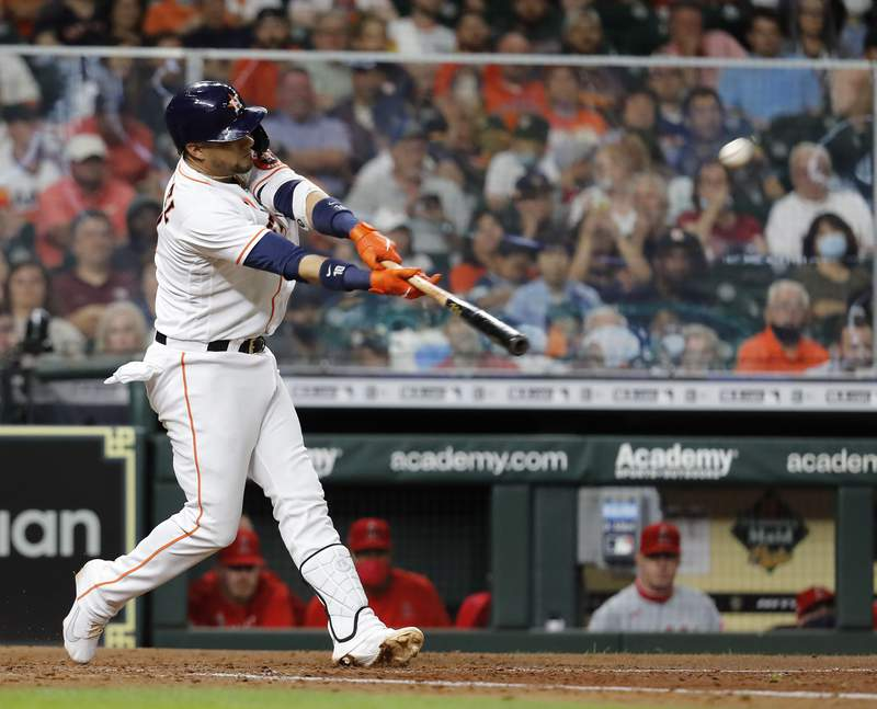 HOUSTON, TEXAS - MAY 11: Yuli Gurriel #10 of the Houston Astros hits a three-run home run in the eighth inning against the Los Angeles Angels at Minute Maid Park on May 11, 2021 in Houston, Texas. (Photo by Bob Levey/Getty Images)
