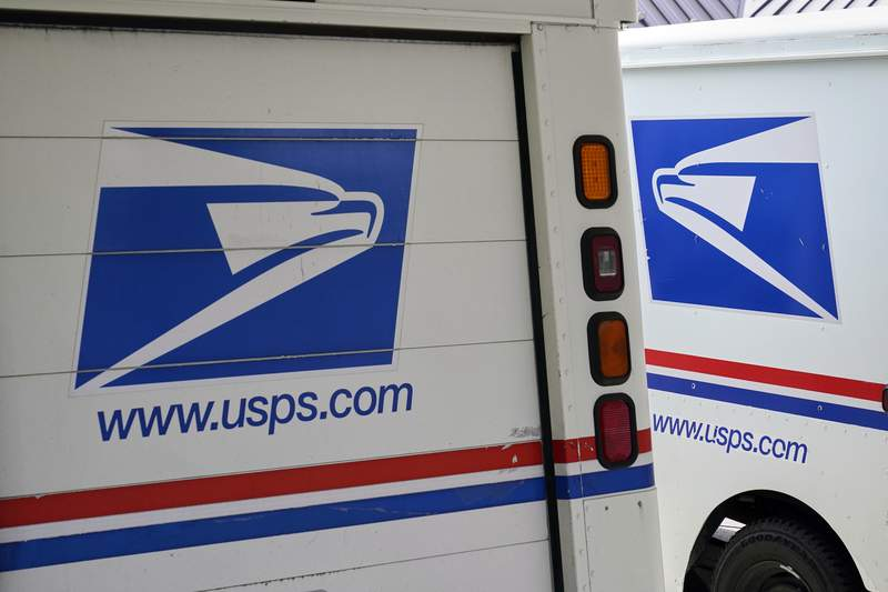 Mail delivery vehicles are parked outside a post office in Boys Town, Neb., Tuesday, Aug. 18, 2020. (AP Photo/Nati Harnik)
