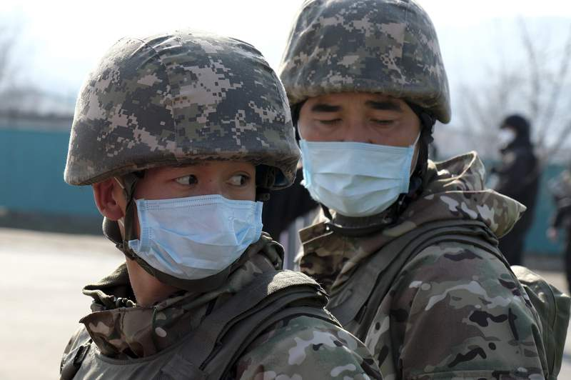 Kazakhstan soldiers wearing face masks block an area in Almaty, Kazakhstan, Thursday, March 19, 2020. A residential block in Almaty, Kazakhstan's former capital and largest city, has been surrounded by the military and blocked for entry and exit after one of the residents was diagnosed with the new coronavirus. For most people, the new coronavirus causes only mild or moderate symptoms. For some it can cause more severe illness. (AP Photo/Vladimir Tretyakov)