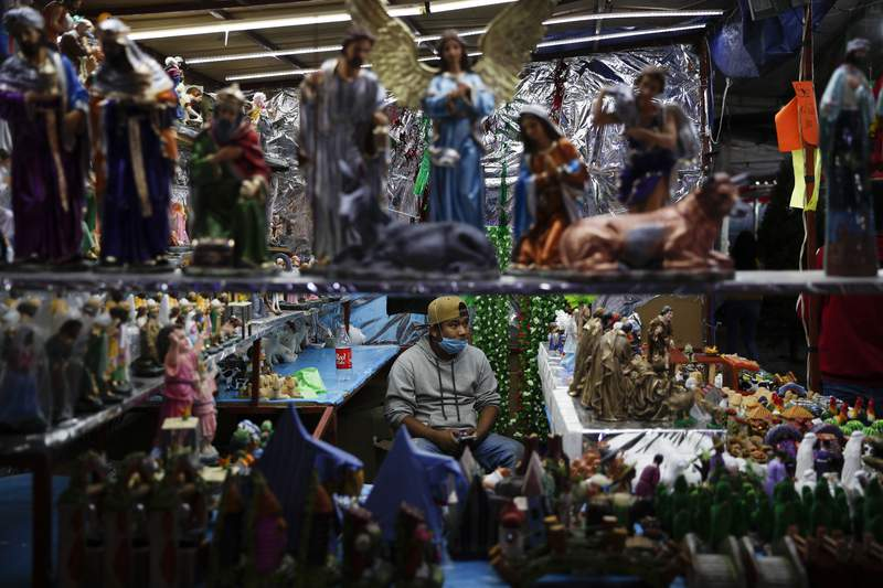 A vendor sells nativity figurines, in a Christmas market where organizers were still deciding if they would close at 5 p.m., in accordance with a new state mandate intended to help slow the spread of COVID-19, in Ecatepec, Mexico State, on the outskirts of Mexico City, Monday, Dec. 14, 2020. Mexico has been posting record increases in coronavirus cases in December, and the capital's hospitals are nearing capacity. (AP Photo/Rebecca Blackwell)