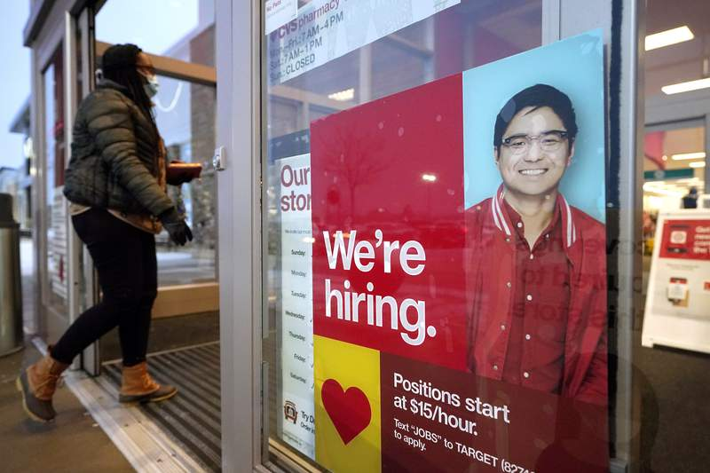 FILE - In this Feb. 9, 2021 file photo, a passer-by walks past an employment hiring sign while entering a Target store location, in Westwood, Mass.   The Federal Reserve says theres evidence that hiring has picked up in recent weeks, though the job market remains badly damaged by the pandemic. In its semi-annual monetary policy report released Friday, Feb. 19, the Fed says job data compiled by payroll processor ADP indicate that employment improved modestly through early February.   (AP Photo/Steven Senne, File)