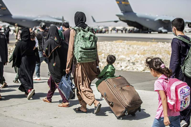 FILE - In this Aug. 24, 2021, file photo, provided by the U.S. Marine Corps, families walk towards their flight during ongoing evacuations at Hamid Karzai International Airport, in Kabul, Afghanistan. A school district in a San Diego suburb that is home to a large refugee population says many of its families who had taken summer trips to Afghanistan to see their relatives have gotten stuck there with the chaos following the withdrawal of U.S. troops. (Sgt. Samuel Ruiz/U.S. Marine Corps via AP, File)
