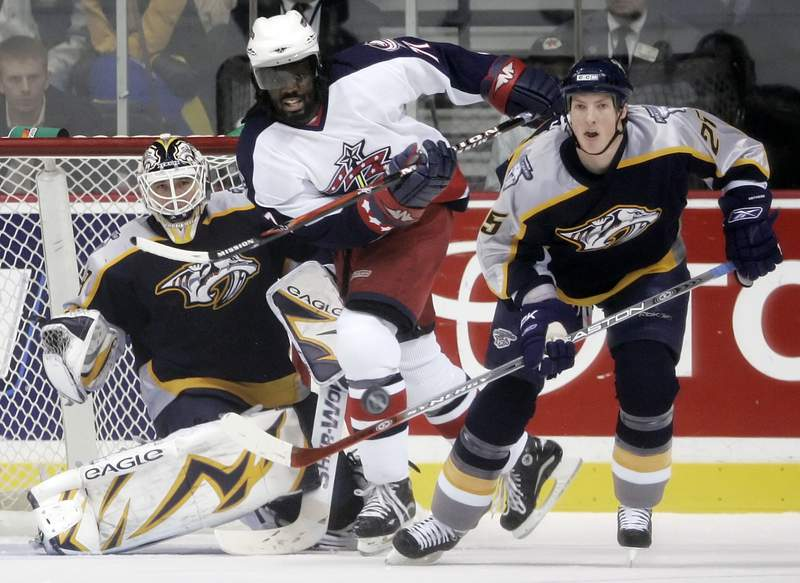 FILE - In this Jan. 12, 2007, file photo, Nashville Predators center Jerred Smithson (25) clears the puck away from Columbus Blue Jackets right wing Anson Carter, center, in the first period of an NHL hockey game in Nashville, Tenn. Carter played a decade in the NHL and has since become an analyst for NBC Sports, which will launch Hockey Culture with him at the center of the show. (AP Photo/Mark Humphrey, File)