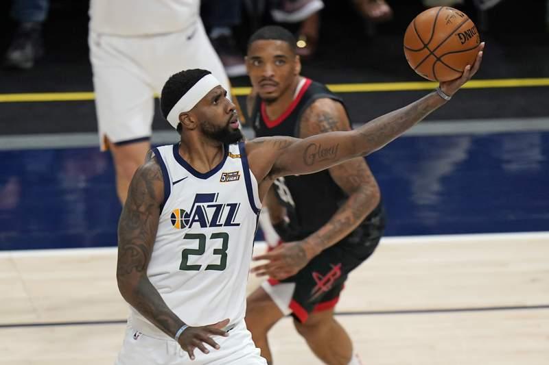 Houston Rockets forward DaQuan Jeffries, rear, looks on as Utah Jazz forward Royce O'Neale (23) lays the ball up during the first half of an NBA basketball game Saturday, May 8, 2021, in Salt Lake City. (AP Photo/Rick Bowmer)