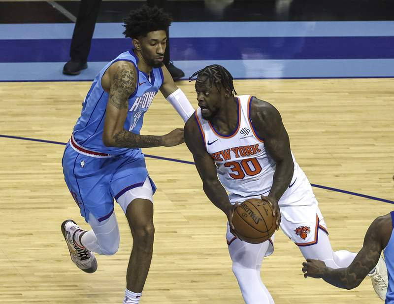 New York Knicks forward Julius Randle (30) drives with the ball as Houston Rockets center Christian Wood (35) defends during the first quarter of an NBA basketball game against the Houston Rockets in Houston, Sunday, May 2, 2021. (Troy Taormina/Pool Photo via AP)