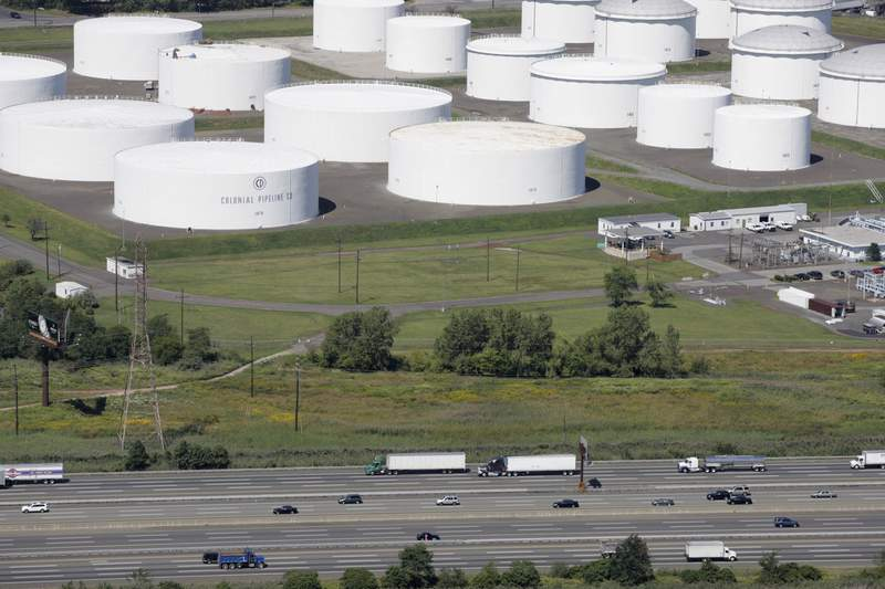 """FILE - In this Sept. 8, 2008 file photo traffic on I-95 passes oil storage tanks owned by the Colonial Pipeline Company in Linden, N.J. A major pipeline that transports fuels along the East Coast says it had to stop operations because it was the victim of a cyberattack. Colonial Pipeline said in a statement late Friday that it """"took certain systems offline to contain the threat, which has temporarily halted all pipeline operations, and affected some of our IT systems."""" (AP Photo/Mark Lennihan, File)"""