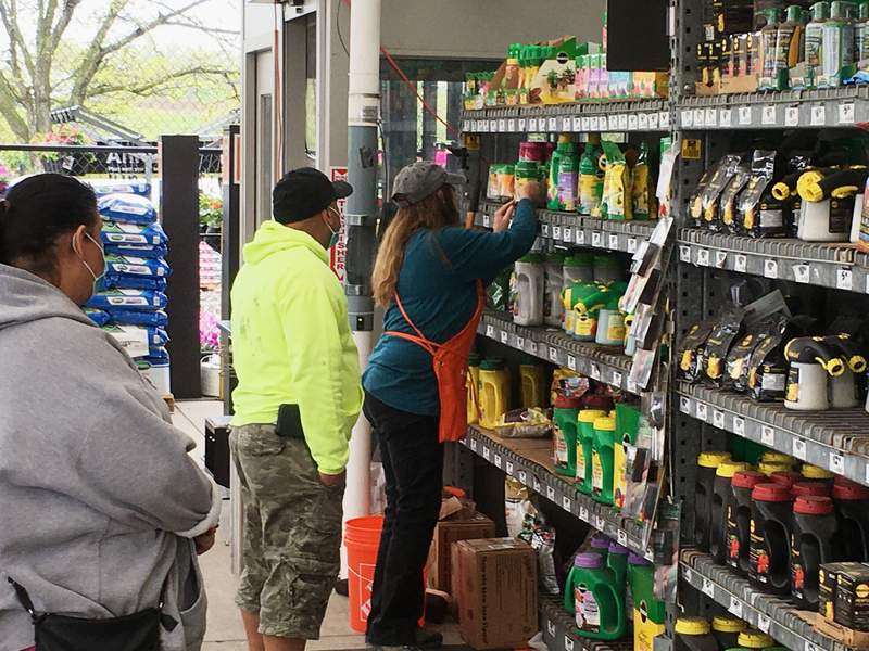 """A clerk assists customers at the garden center at a Home Depot store in Harrisburg, Pa., on Wednesday, May 6, 2020. As swaths of Pennsylvania prepare for a limited reopening Friday, some fed-up business owners are jumping the gun and have resumed serving customers in defiance of Gov. Tom Wolfs shutdown order. Home Depot said Wednesday that """"many essential items"""" are in the outside garden area of its stores, including building materials, retaining walls, and drainage and repair products. (AP Photo/Mark Scolforo)"""
