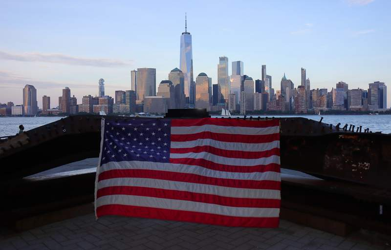 An American flag hangs on a piece of steel on a memorial to the Sept. 11 attacks on the World Trade Center in front of lower Manhattan and One World Trade Center in New York City on Aug. 16, 2021 in Jersey City, New Jersey.