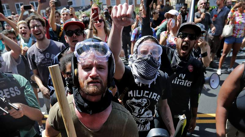 """Anti-fascist counter-protesters wait outside Lee Park to hurl insluts as white nationalists, neo-Nazis and members of the """"alt-right"""" are forced out after the """"Unite the Right"""" rally was declared an unlawful gathering August 12, 2017 in Charlottesville, Virginia. As protests over George Floyd's death spread across the country, officials have blamed the violent nature of some demonstrations on members of a controversial group known as Antifa. (Chip Somodevilla/Getty Images)"""