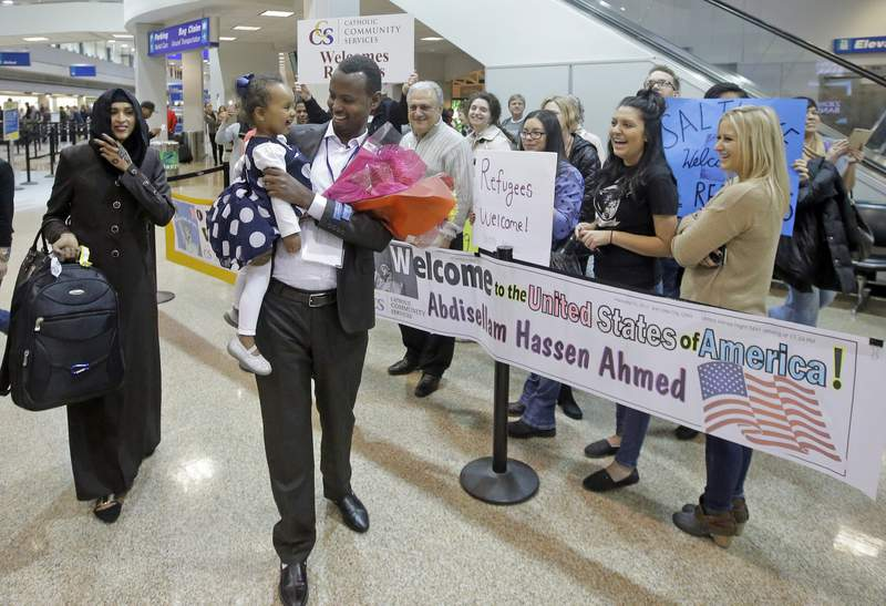 FILE - This Feb. 10, 2017, file photo, Abdisellam Hassen Ahmed, a Somali refugee who had been stuck in limbo after President Donald Trump temporarily banned refugee entries, walks with his wife Nimo Hashi, and his 2-year-old daughter, Taslim, who he met for the first time after arriving at Salt Lake City International Airport. President Trump appears to be ignoring a deadline to establish how many refugees will be allowed into the United States in 2021, raising uncertainty about the future of the 40-year-old resettlement program that has been dwindling under the administration. The 1980 Refugee Act requires presidents to issue their determination before Oct. 1, 2020, the start of the fiscal year. (AP Photo/Rick Bowmer, File)