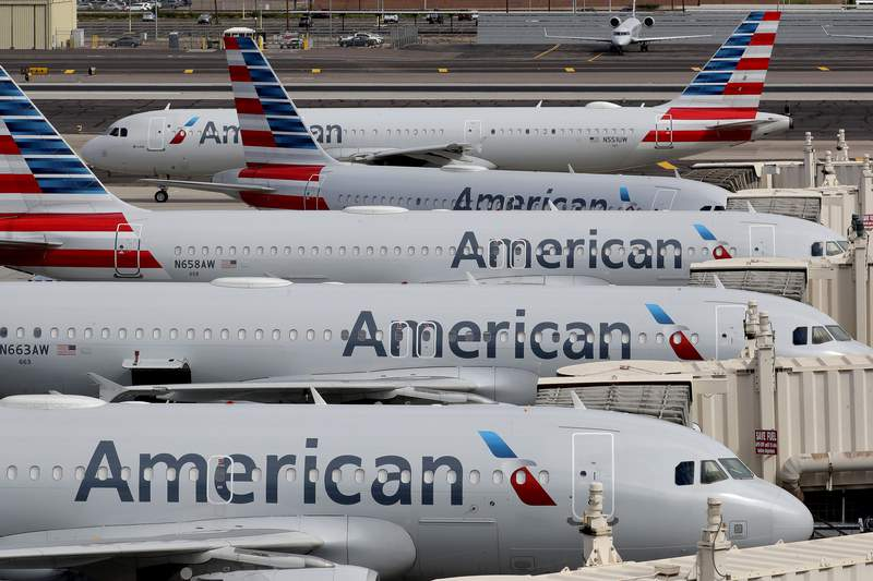 FILE - In this Wednesday, March 25, 2020 file photo, American Airlines jets sit idly at their gates as a jet arrives at Sky Harbor International Airport in Phoenix. The Trump administration is raising the possibility of the U.S. government getting ownership stakes in U.S. airlines in exchange for $25 billion in direct grants to help the carriers survive a downturn caused by the coronavirus pandemic, according to people familiar with the matter, Thursday, March 26, 2020. (AP Photo/Matt York, File)