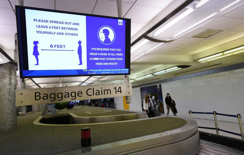FILE - In this Dec. 10, 2020, file photo, an electronic sign warns travelers to maintain social distance in the terminal of Denver International Airport in Denver. About one-fifth of flight attendants say they've gotten into a physical incident with a passenger this year. That's according to a survey by their union. The Association of Flight Attendants says it wants people who act up during flights to face criminal prosecution  not just fines. Airlines have reported more than 3,600 cases of unruly passengers this year. Disputes over face masks are the most common trigger. Federal rules require face masks on planes until mid-Sept (AP Photo/David Zalubowski, File)