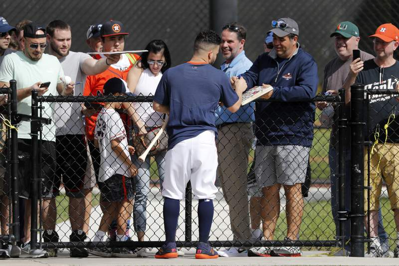 Houston Astros' Jose Altuve signs autographs during spring training baseball practice Thursday, Feb. 13, 2020, in West Palm Beach, Fla. (AP Photo/Jeff Roberson)