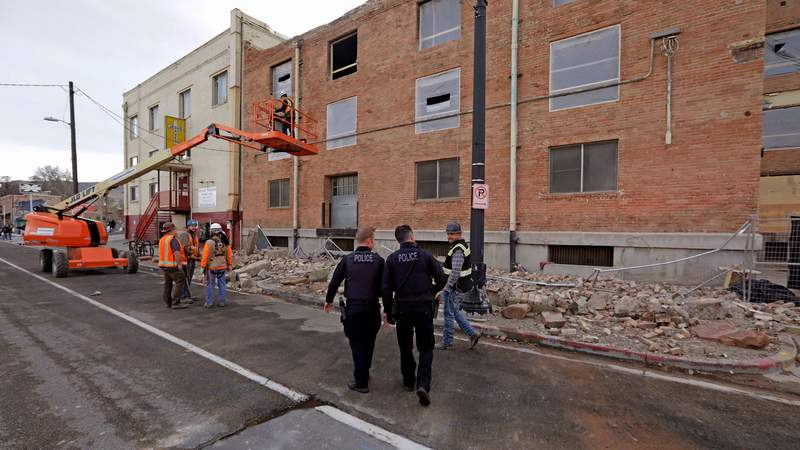 Police officers walk pass rubble after an earthquake Wednesday, March 18, 2020, in Salt Lake City.   A 5.7-magnitude earthquake has shaken the city and many of its suburbs. The quake sent panicked residents running to the streets, knocked out power to tens of thousands of homes and closed the city's airport and its light rail system.   (AP Photo/Rick Bowmer)