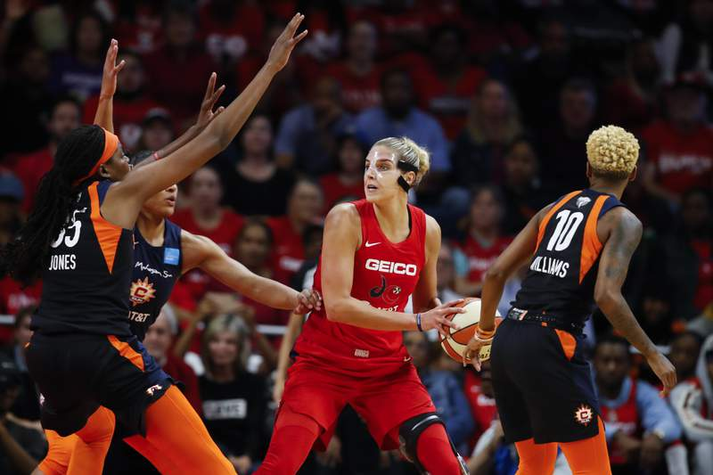 FILE - In this Oct. 10, 2019, file photo, Connecticut Sun forward Jonquel Jones, left, and guard Courtney Williams, right, huard Washington Mystics forward Elena Delle Donne during the first half of Game 5 of basketball's WNBA Finals in Washington. Delle Donne is waiting to have her case heard by the league's independent panel of doctors to see if she'll be medically excused for the season, according to the Mystics.  The Mystics star, who was the league Most Valuable Player last year, has battled Lyme Disease since 2008 and would potentially be at a higher risk for serious illness if she contracted the new coronavirus. (AP Photo/Alex Brandon, File)