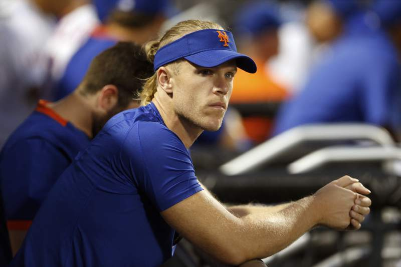 FILE - In this Aug. 14, 2021, file photo, New York Mets pitcher Noah Syndergaard watches play against the Los Angeles Dodgers during the first inning of a baseball game in New York. A person familiar with the situation tells The Associated Press that Syndergaard has tested positive for COVID-19. Syndergaard was scratched from a rehab start on Sunday, Aug. 29, 2021. The person spoke on condition of anonymity because the team has not disclosed the positive test. (AP Photo/Noah K. Murray, File)