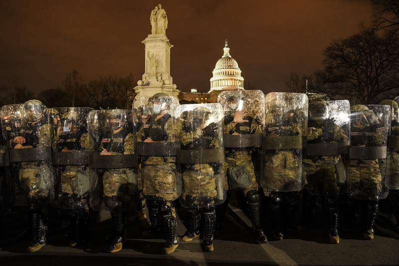 District of Columbia National Guard stand outside the Capitol, Wednesday night, Jan. 6, 2021, after a day of rioting protesters. It's been a stunning day as a number of lawmakers and then the mob of protesters tried to overturn America's presidential election, undercut the nation's democracy and keep Democrat Joe Biden from replacing Trump in the White House. (AP Photo/John Minchillo)