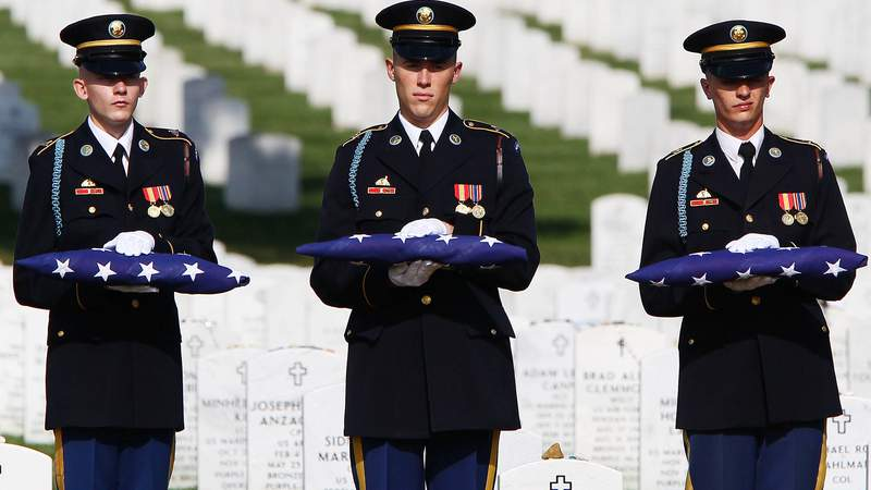 A U.S. Army honor guard team hold American flags to be given to family members at the burial service for Staff Sgt. Edwardo Loredo, at Arlington National Cemetery July 27, 2010 in Arlington, Virginia. Staff Sgt. Loredo, from Houston, Texas, was killed by an improvised explosive device during a dismounted operation in the Arghandab River Valley in Afghanistan.