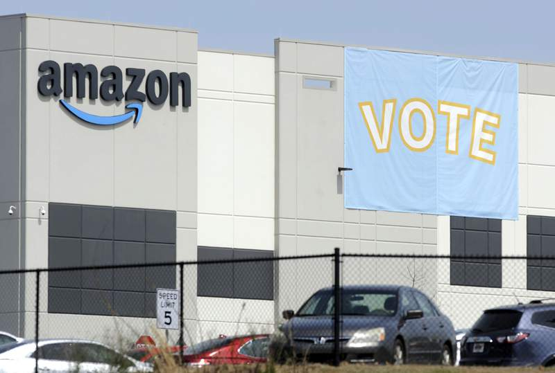 FILE - In this Tuesday, March 30, 2021 file photo, a banner encouraging workers to vote in labor balloting is shown at an Amazon warehouse in Bessemer, Ala.  Vote counting in the union push  in Bessemer is expected to start as early as Thursday, April 8, but hundreds of contested ballots could muddy the outcome if its a close race.   (AP Photo/Jay Reeves, File)