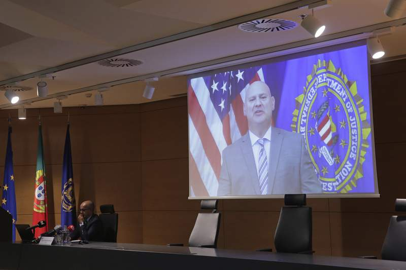 FBI Pittsburgh Special Agent Michael Christman speaks in a video presented by Portuguese police chief inspector Paulo Goncalves, at left, during a news conference at the police headquarters in Lisbon, Thursday, Oct. 15, 2020. European and American officials say that they have arrested 20 individuals for allegedly belonging to an international ring that laundered millions of euros stolen by cybercriminals in an international police operation led by Portuguese investigators and the F.B.I. (AP Photo/Armando Franca)