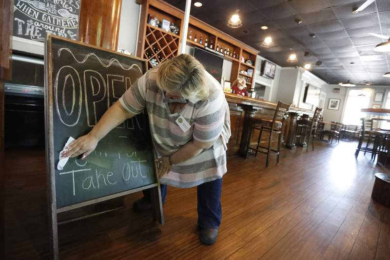 Mary Spoto, general manager of Madison Chop House Grille, changes the sign as she and her staff prepare to shift from take out only to dine-in service Monday, April 27, 2020, in Madison, Ga. Some Georgia restaurants were reopening for limited dine-in service as more restrictions against the coronavirus are loosened in the state. Movie theaters on Monday can welcome customers and limited in-restaurant dining may resume. (AP Photo/John Bazemore)