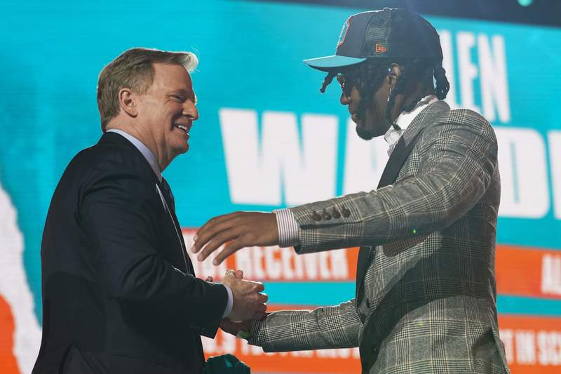 Alabama wide receiver Jaylen Waddle, right, greets NFL Commissioner Roger Goodell after being chosen by the Miami Dolphins with the sixth pick in the NFL football draft Thursday April 29, 2021, in Cleveland. (AP Photo/Tony Dejak)
