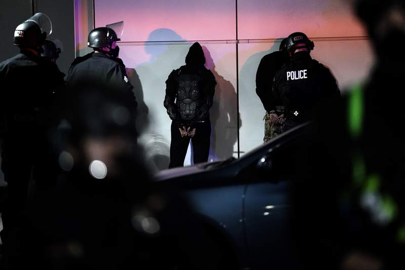 A man is detained by police on Election Day, Tuesday, Nov. 3, 2020, in Los Angeles. (AP Photo/Jae C. Hong)