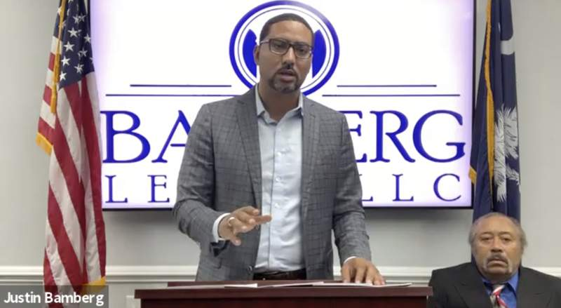 In this screen grab from video provided by Bamberg Law, LLC, attorney Justin Bamberg, standing, speaks at a news conference as plaintiff Jethro DeVane, seated at right, listens, Tuesday, Dec. 22, 2020, in Orangeburg, S.C. DeVane was embarrassed and feared for his life during a June 2019 episode when a Rock Hill police officer looking for teens who might have been breaking into cars held him outside naked and at gunpoint after he peeked out his door to check on the disturbance. (Courtesy of Bamberg Law, LLC via AP)