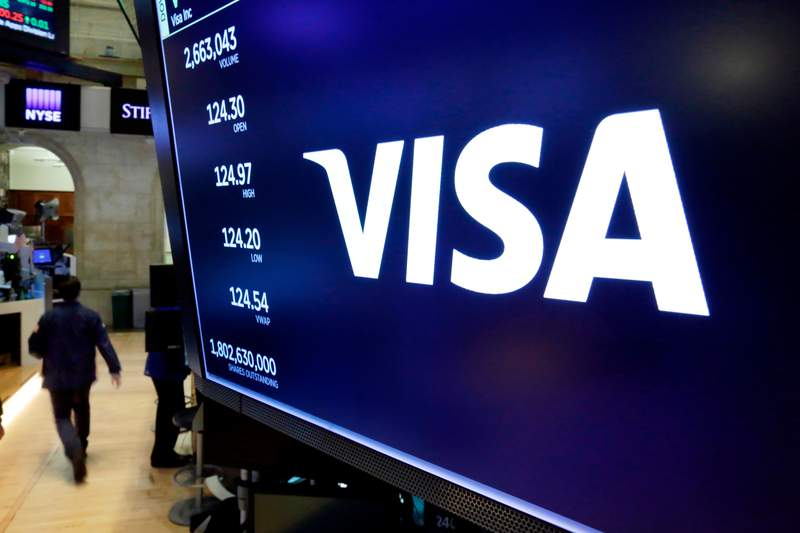 FILE- In this April 23, 2018, file photo, the logo for Visa appears above a trading post on the floor of the New York Stock Exchange. Visa Inc. said Wednesday, Oct. 28, 2020, that its fiscal fourth quarter profits dropped 29% due to fewer dollars crossing on its namesake payment network while the world was in the grips of a pandemic-caused recession. (AP Photo/Richard Drew, File)